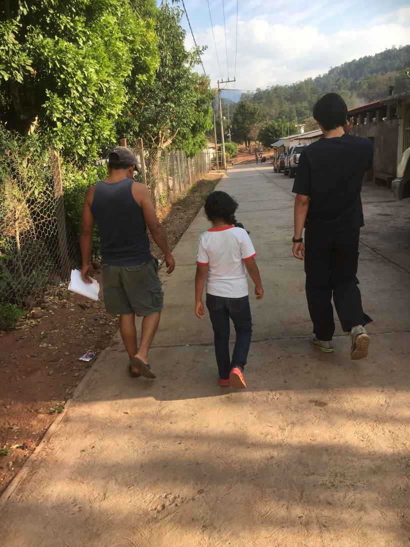 Dr. Ivan Martinez walks back to the clinic with a father and daughter discussing their recent illness. Impromptu consults are common.
